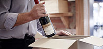 Image of a man packaging wine in a box