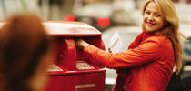 Happy woman posting mail in the red post box