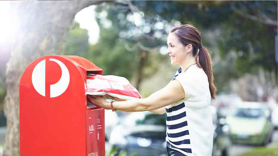 Woman putting her parcel into a red street posting box.