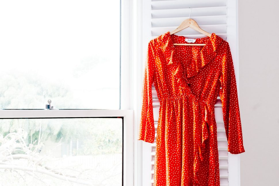 Woman standing by a window with a dress hanging up against a frame. The woman is holding the dress hem in one hand and smoothing the waist with her other hand - making sure the dress lays out nicely.