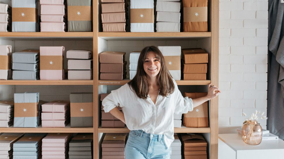 Hayley Worley, owner of The Sheet Society; A smiling young woman in a white shirt and blue jeans standing in front of tall wooden shelves stacked with various bed sheets.