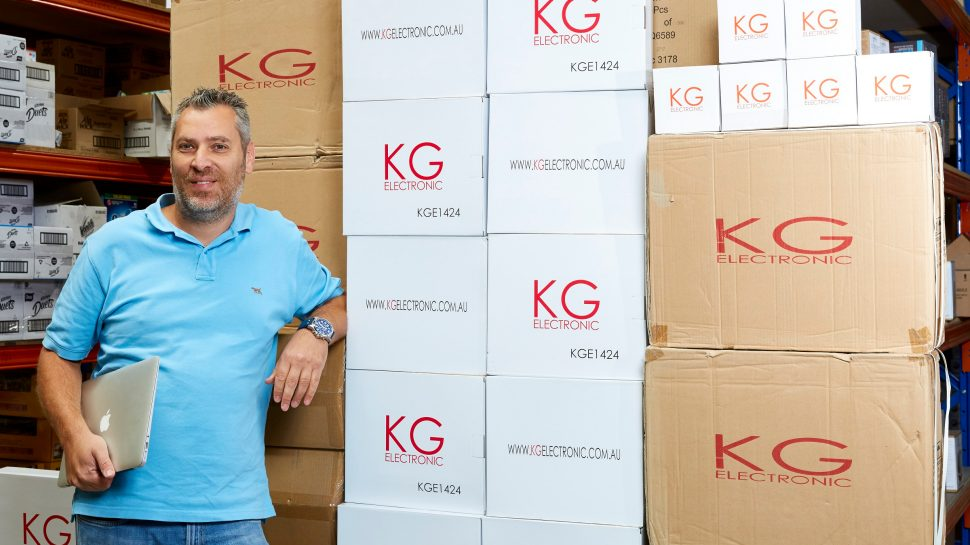 Doron Kushlin standing in front of boxes in the warehouse of KG Electronics
