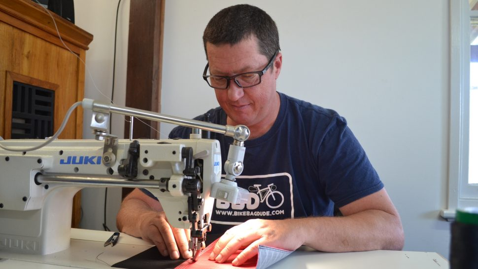 Kedan Griffin at the sewing machine sewing a custom bag