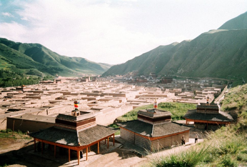 A birds-eye-view of the Labrang Monastery in Xiahe. The countless number of the maze-like buildings expands into the distance, with grass-covered mountains canvassing either side of the small city.