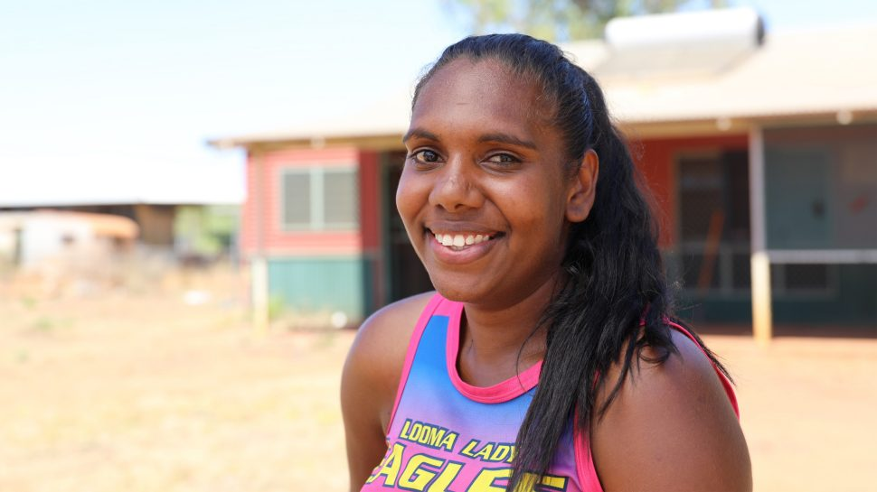 A young Indigenous woman wearing a pink singlet with the words Looma Lady Eagles written on it