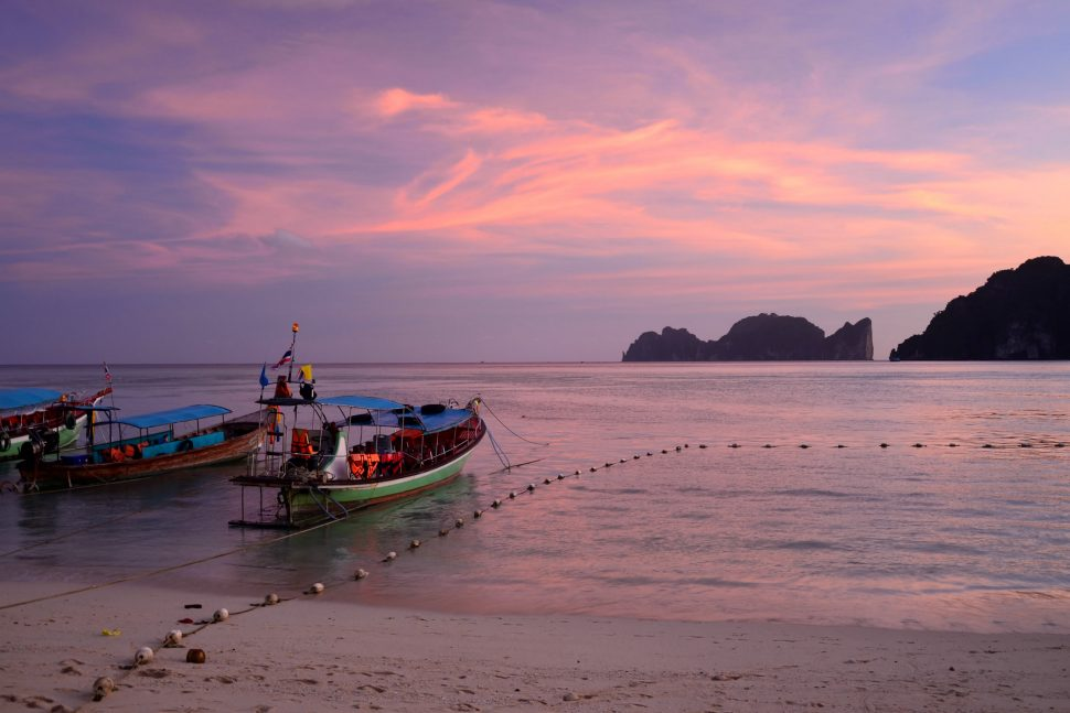 Ko Phi Phi Don beach (largest of the Phi Phi Isalnds in the Krabi province, Thailand) at sunset, with two boats docked in shallow waters in the foreground.