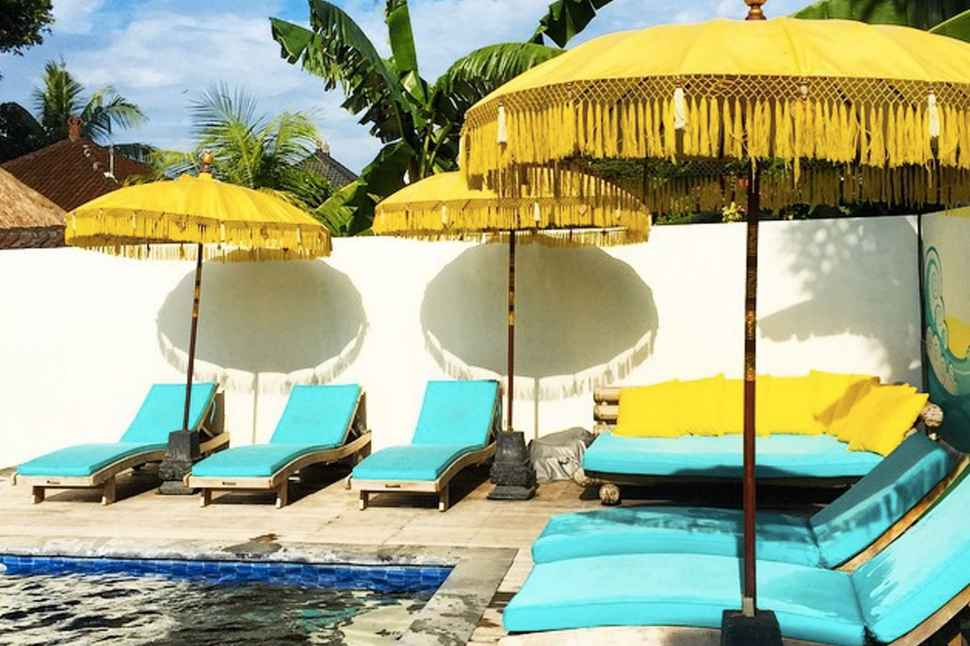 At the Chill House, bright blue deckchairs and lounges sit under yellow umbrellas around an empty pool, clear skies are in the background.