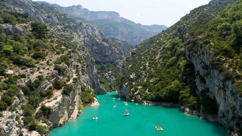 A panoramic view of the Verdon Gorge in France. Azure, still water runs through the middle of this scene, subtly winding through the rock formations that surround it. Huge rocks forming the gorge stand tall to both the left and right. There's dense shrubbery forming on the rocks. People can be seen kayaking through the crystal blue water.